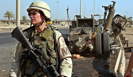 A female US soldier stands in front of the wreckage of an US army truck