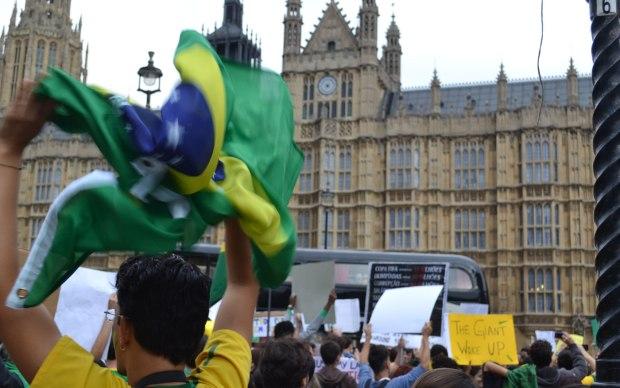 Manifestante agita bandeira brasileira em protesto em Londres, na terça (18).