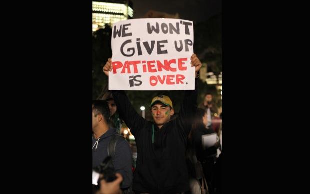 Manifestante protesta em Sydney com cartaz que diz- 'não vamos desistir. A paciência acabou.