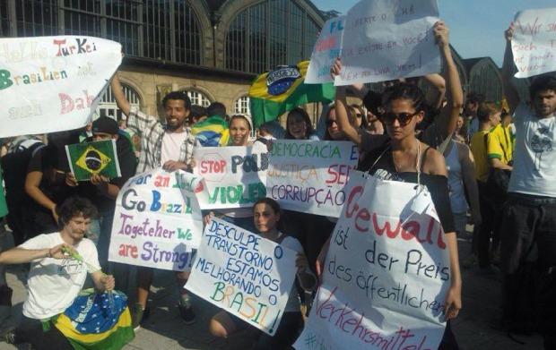 Manifestantes brasileiros carregam cartazes durante protesto em Hamburgo, na Alemanha.