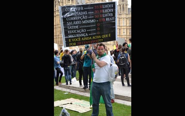 O brasileiro Vitor Paiva carrega cartaz durante protesto em Londres.